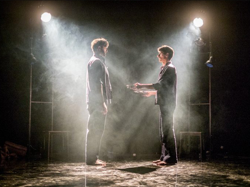 Due attori di fronte in scena. due faci di luce su di loro