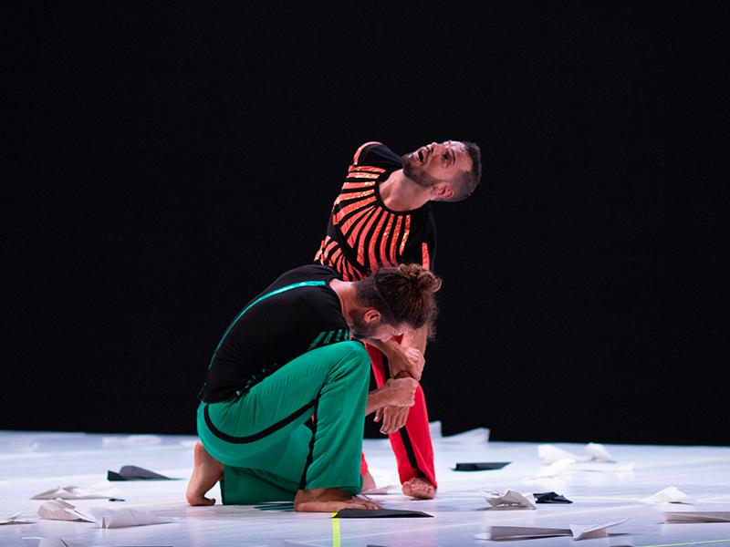 sfondo nero. Su un palco bianco i due danzatori indossano uno vestiti neri e rossi mentre l'altro vestiti neri e verdi. Ballano e sul pavimento degli aeroplanini di carta.