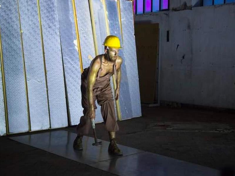 il danzatore è vestito come un minatore e indossa un casco giallo da cantiere. Il corpo e il viso sporchi di fuliggine. In mano tiene un grosso martello.