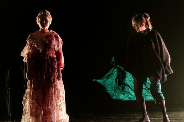 due donne, una in abito rosa, altra ha un mantello verde