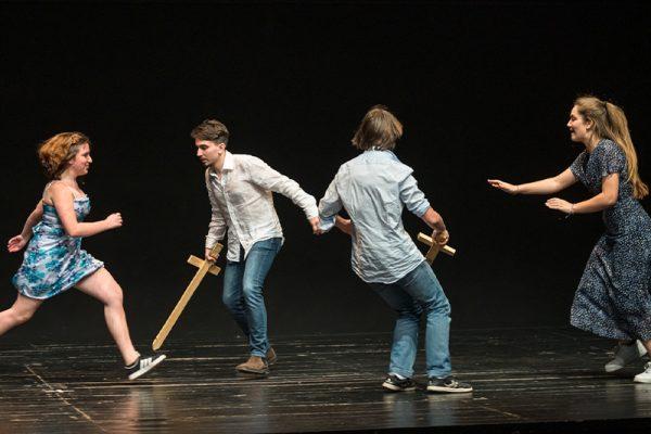 due ragazzini in camicia e jeans duellano con spade di legno