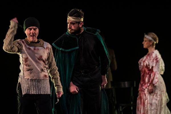 un uomo con una corona e un abito verde fra altri due attori