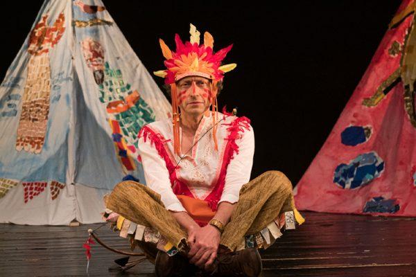 un allievo seduto a gambe incrociate e vestito da capo indiano. sullo sfondo un tepee