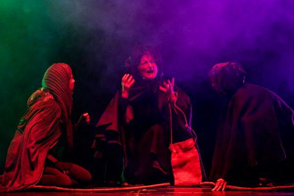 tre attori in scena con fumo e luci viola