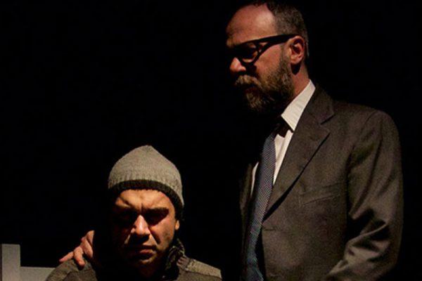 un attore seduto, altro in piedi con una mano sulla spalla