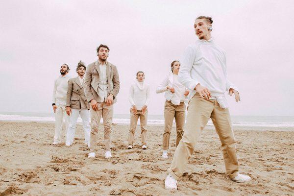 Sei danzatori si trovano su una spiaggia sabbiosa, sullo sfondo il mare e un cielo coperto, quasi bianco. Indossano abiti chiari con toni che si adeguano al paesaggio che li circonda. Indossano delle cuffie.