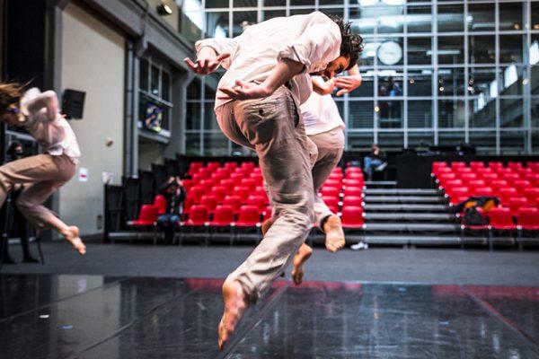 un danzatore in primo piano e due sullo sfondo sono immortalati nella loro danza durante un salto. Dietro di loro una sala teatrale.