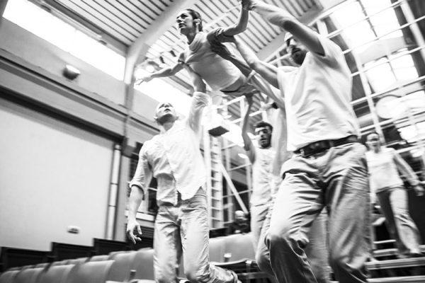 foto in bianco e nero: i danzatori sorreggono una danzatrice in una posizione simile alla presa dell'angelo. Dietro di loro una sala teatrale.