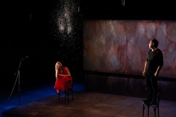 attrice in abito rosso su una sedia