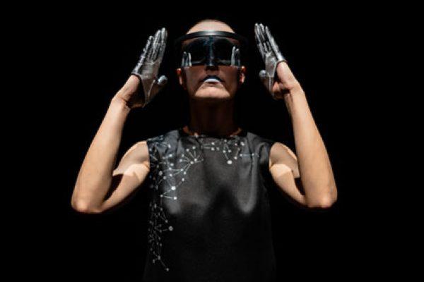 attrice con visiera e trucco azzurro in posizione robotica