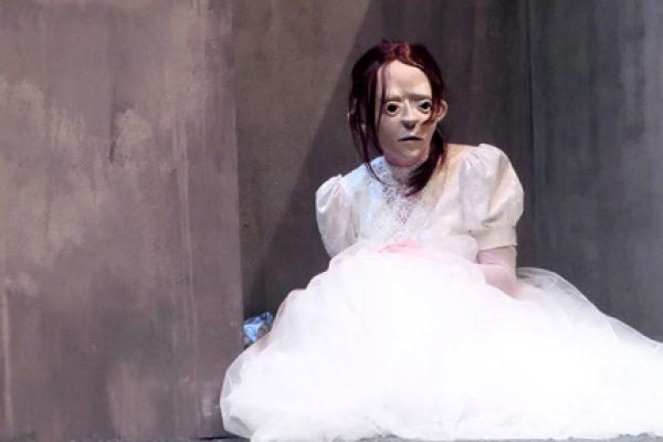 attrice in abito bianco che indossa maschera Floez