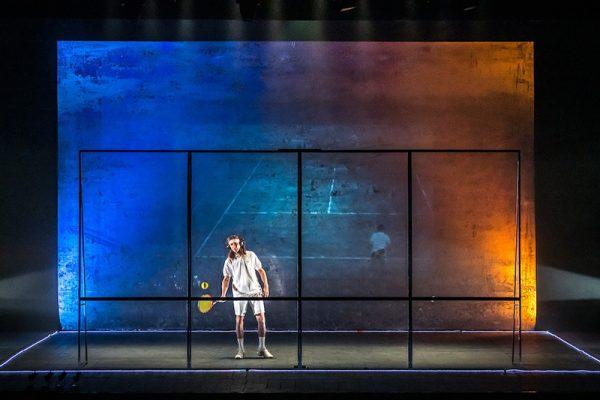 sulla scena un tennista dietro la parete di plexiglass