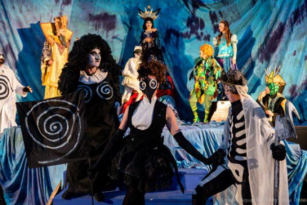 scena corale: in prima fila madre ubu, la gazza ladra e la morte, dietro, su una scena azzurra, ci sono la regina della notte, papageno, pamina