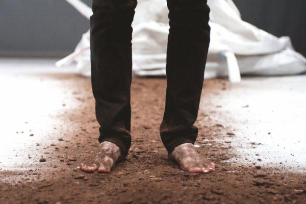 le gambe di un uomo a piedi nudi e sulla terra sparsa in scena