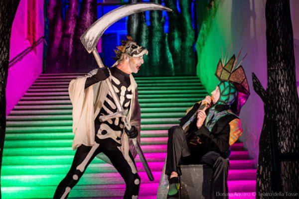 attore che interpreta la morte minaccia di colpire con la falce l'attore che interpreta il serpente uroboro