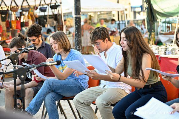 ragazzi seduti leggono in una piazza