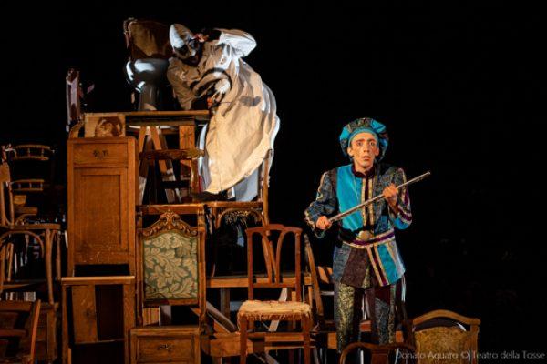 scena composta da una montagna di sedie. in cima Ubu Re, sotto Tamino con il flauto magico