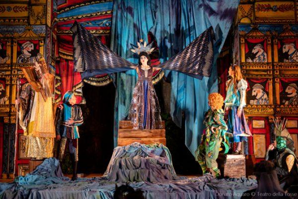 scena con drappo azzurro e attori in costume. Al centro La Regina della Notte