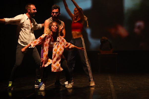 un ballerino vestito street style in primo piano compie un salto. Sullo sfondo quattro ballerini e la proiezione.