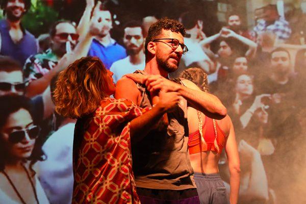 in primo piano due ballerini in abiti street style. Sullo sfondo la proiezione di una folla.