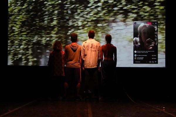 quattro ballerini di schiena guardano la proiezione sullo sfondo