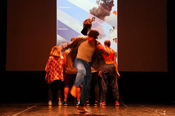 in primo piano quattro ballerini in abiti street style. Sullo sfondo una proiezione.