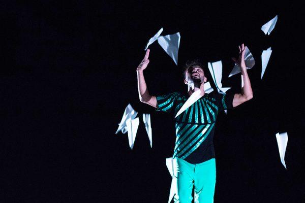 sfondo nero. In primo piano un ragazzo (il danzatore) indossa vestiti di colore nero e verde e lancia in aria degli aeroplanini di carta.