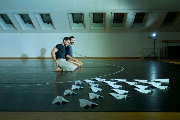 i due danzatori siedono a terra e davanti a loro in primo piano sono disposti degli aeroplanini di carta.