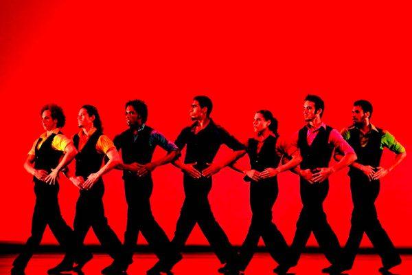 danzatori in fila per mano, sfondo di luce rossa