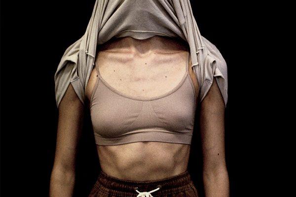 busto di donna in reggiseno sportivo e testa coperta dalla maglietta