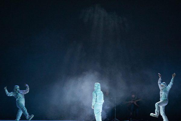 tre persone in tuta spaziale sul palco