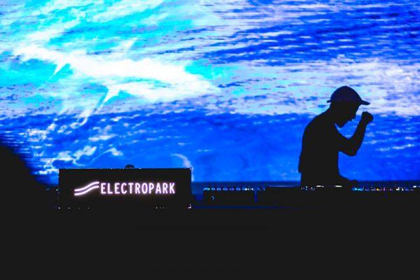 sullo sfondo una proiezione visual sui toni del blu. In controluce un djset con una persona in piedi e il logo di electropark.