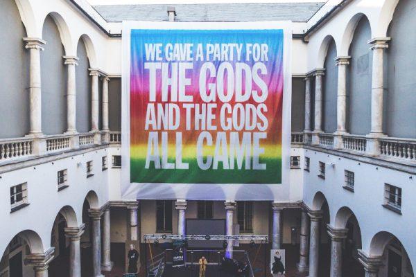 """in un cortile loggiato ritratto in prospettiva centrale, in basso un djset con diverse persone e appeso un grande manifesto color arcobaleno con la scritta: WE GAVE A PARTY FOR THE GODS AND THE GODS ALL CAME"""""""