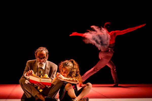 due danzatori seduti leggono sullo sfondo un terzo con costume di piume