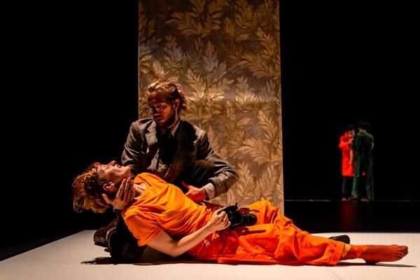 un danzatore sdraiato in abiti arancioni. un secondo gli regge la tasta