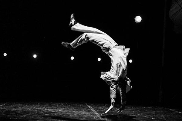 foto in bianco e nero: su un palco semibuio una luce illumina un danzatore mentre compie un'acrobazia.