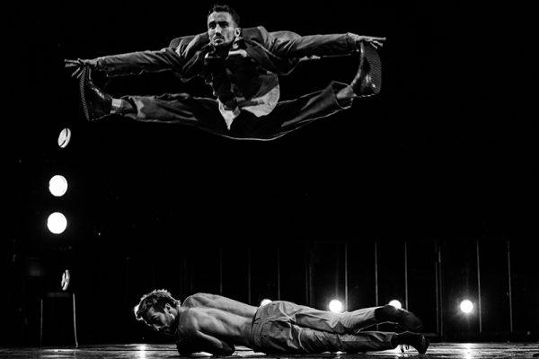 foto in bianco e nero: su un palco semibuio un uomo compie una spaccata in aria mentre un altro è sdraiato a terra sotto di lui.