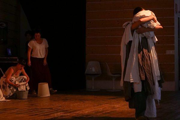 in primopiano uno donna coperta di panni da lavare, sullo sfondo una seconda con un secchio
