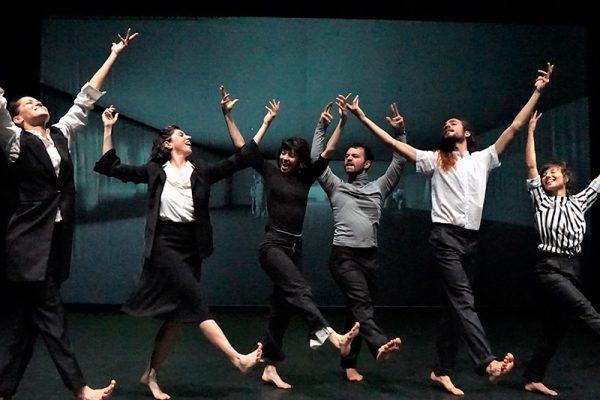 scena corale di danzatori con le braccia alzate