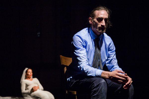 Danzatore in abito cravatta seduto su una sedia di legono, la danzatrice è sullo sfondo in ginocchio e in abito da sposa
