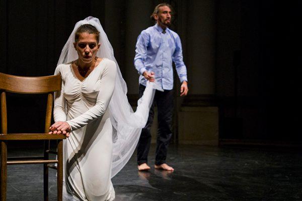 danzatrice in ginocchio in abito da sposa, lo sposo, in secondo piano regge il velo