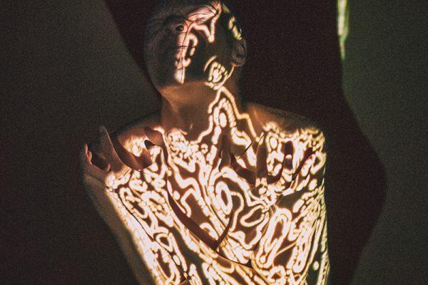 un corpo e delle scritte di luce sul corpo