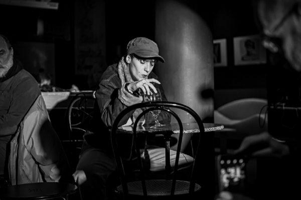 foto in bianco e nero: una ragazza (la danzatrice) indossa giacca e cappellino con visiera. siede ad un tavolino di un bar bevendo un cocktail