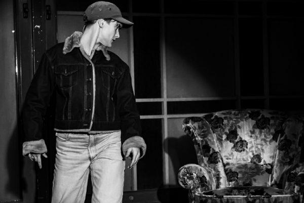 foto in bianco e nero: una ragazza (la danzatrice) indossa giacca,jeans e cappellino con visiera. È in piedi e guarda una poltrona vuota.