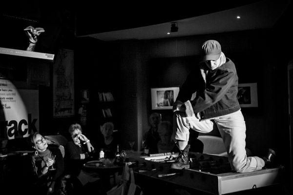 foto in bianco e nero: una ragazza (la danzatrice) indossa giacca,jeans e cappellino con visiera. È inginocchiata su un tavolo da calcetto. Sullo sfondo il pubblico.
