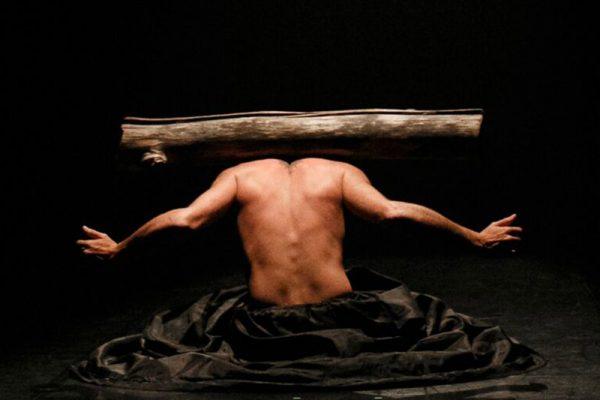 in uno spazio buio si staglia la schiena nuda del danzatore. Le sue spalle sorreggono in equilibrio un grosso tronco di albero.
