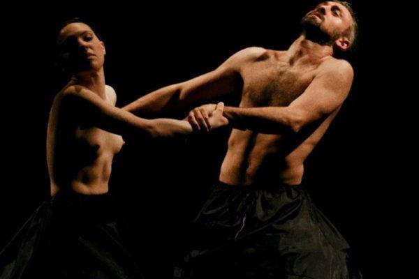 in uno spazio buio i due danzatori indossano costumi neri che coprono la parte del corpo dal bacino in giù. Sono immortalati mentre danzano e si tengono per le mani.