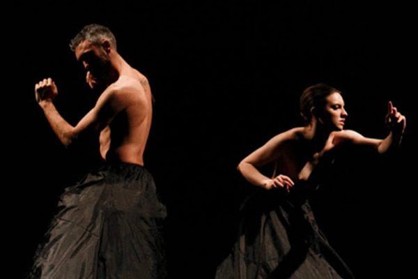 in uno spazio buio i due danzatori indossano costumi neri che coprono la parte del corpo dal bacino in giù. Sono immortalati in pose di danza.