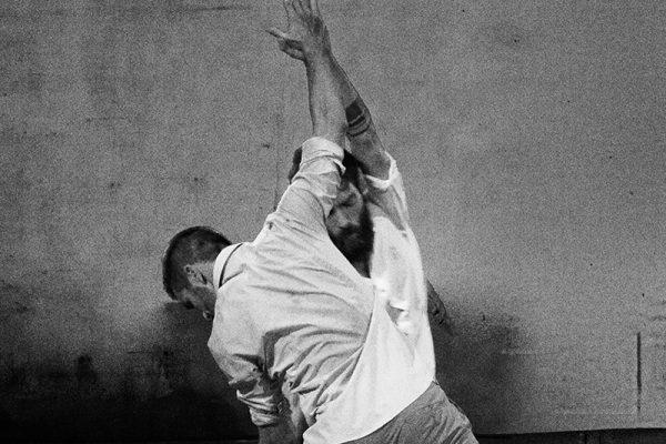 foto in bianco e nero: i due danzatori indossano camicie bianche e vengono immortalati in una posa di danza. I palmi delle loro mani si toccano.