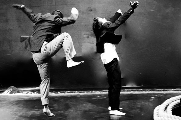 foto in bianco e nero: i due danzatori vengono immortalati mentre danzano; uno dei due è immortalato durante un salto.